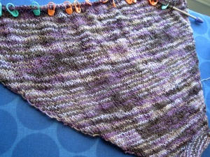 My unfinished Clapotis scarf, in a variegated purple, black, and grey yarn.